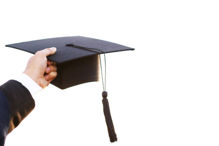 A person holding a graduation cap in the air