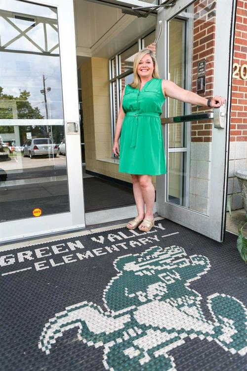 Mrs. Amy Gregory, principal standing at the front door to Green Valley Elementary