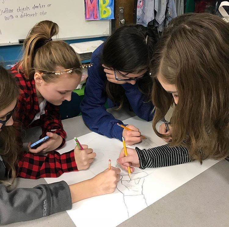 This is a picture of the art club students drawing a picture.