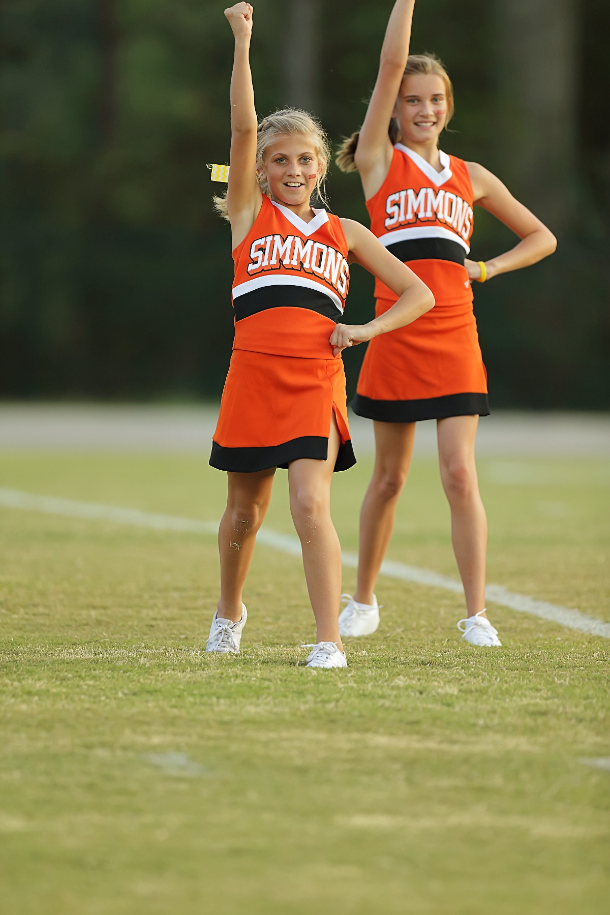 This picture is of 2 7th grade cheerleaders during a football game.