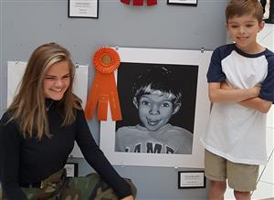 Olivia pictured next to her portrait of her little brother with him standing by.