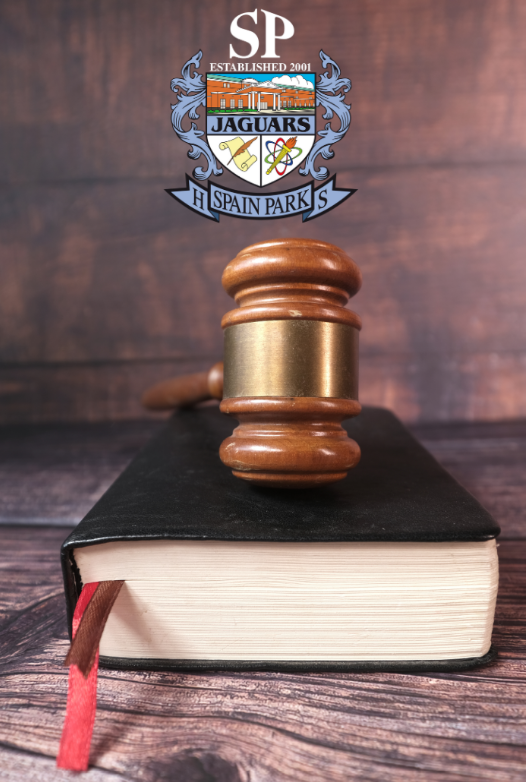 A gavel on top of a book sitting on top of a wooden table with the Spain Park High School Logo