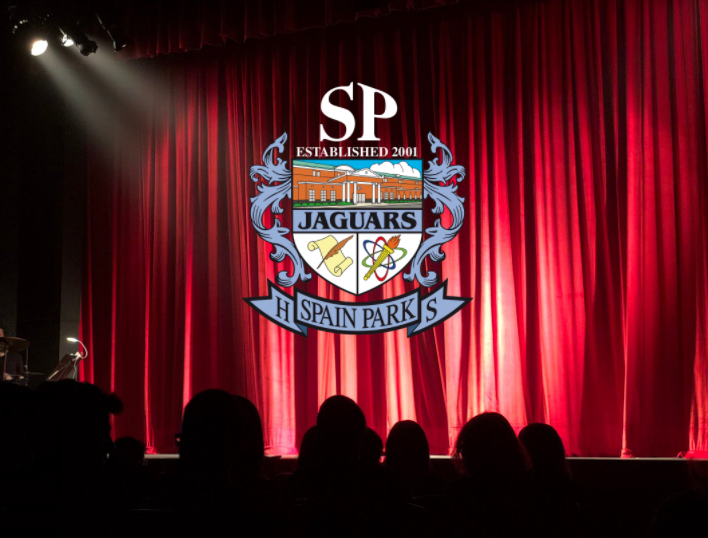 People sitting in a theater with the Spain Park Logo on the Red Curtains